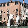 Gigantic stony hands rise from the Grand Canal in an environmental plea