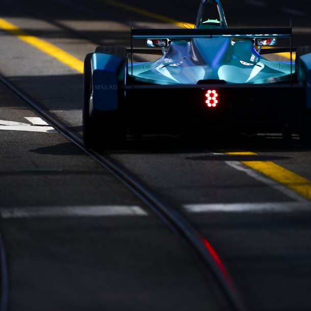 formula_e_car_on_track_making_its_way_through_the_shadows_with_the_rear_light_illuminated